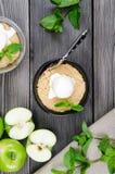 Fine di vista superiore sul dessert della briciola di Apple con gelato alla vaniglia, menta verde sulla tavola di legno grigia fo immagine stock