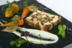 Fine dining. Restaurant starter of pressed chicken terrine with baby vegetables, shallow dof Royalty Free Stock Photos