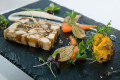 Fine dining. Restaurant starter of pressed chicken terrine with baby vegetables, shallow dof Royalty Free Stock Photography