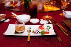 Fine Dining. A fine dining seafood and salad presentation on a square plate on a red table cloth and background of wine glass and a soft drink Stock Image