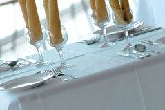 Fine dining. Table at restaurant set up for 3 course meal with white linen tablecloth ,white china dinner set , cutlery and yellow napkins royalty free stock image