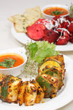 Fine dining meal, chicken shish kebab. Chicken shish kebab with indian sauce and eggplant served with rucola salad and naan bread Stock Image
