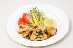 Fine dining meal, fresh squid. Squid in company of lemon and tomatoes served on a plate with garlic, butter and parsley Royalty Free Stock Images