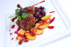 Fine dining meal roast duck with apples. Roast duck hetman-style served with apples, young cabbage and cranberry wine sauce Royalty Free Stock Images