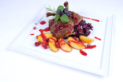 Fine dining meal -Roast duck with apples cranberry. Roast duck hetman-style served with apples, young cabbage and cranberry wine sauce Gebratene Ente auf Art des stock images