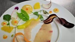 Fine dining platter fish snow peas radish stock images