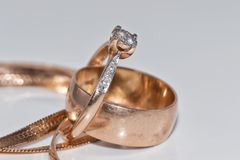 Fine elegant Golden ring with diamond and gold chain. Thin elegant gold diamond ring, thick wedding ring and a gold chain with a snake tribe on a white Royalty Free Stock Photos
