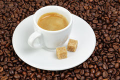 Fine espresso in cup on coffee beans Royalty Free Stock Images