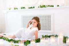 Fine figured girl lying elegantly in a white room with green leaves all around her, eyes down, hand touching thick hair. Health royalty free stock photography