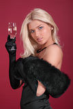 The fine girl. Portrait of the fine woman in an evening dress with a wine glass on a red background Stock Photo