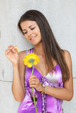 Fine girl. The girl in a lilac dress guesses on a flower Gerbera Royalty Free Stock Photography