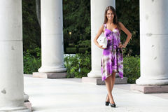 Fine girl. The girl in a lilac dress stand about a columns Stock Photography