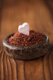 Fine grated chocolate and heart marshmallow candy in iron bowl Stock Photos