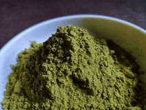 Green tea powder in the plate on the wooden table. Fine green tea powder in a white cup on a wooden table royalty free stock image