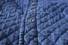 Fine imbottita di struttura dell'elemento del panno del denim del tessuto su con i bottoni del metallo immagini stock