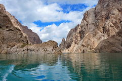 Fine Kelsu mountain lake with grandiose rocks and. The dark blue sky with clouds... Kelsu, Kyrgyzstan Royalty Free Stock Image
