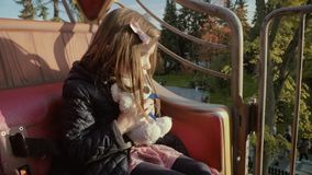 Brave girl rides on a roundabout, looks and turns around with her teddy bear at sunset in slo-mo stock video footage