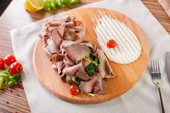 Fine meats with herbs and sauce. On a wooden board Stock Photography