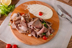 Fine meats with herbs and sauce. On a wooden board Stock Images