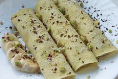 Fine morbida del fuoco su di 3 pancake di crêpe con le banane completate con i trucioli dei cocos e del cioccolato ed i pistacchi fotografia stock