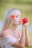 Fine perfume petals. Long-haired blonde inhales the aroma of petals stock image