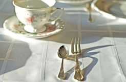 Fine porcelaine cup and silver cutlery on table. Table set with white tablecloth and china. Fine porcelaine coffee cup and silver cutlery closeup in short focus Royalty Free Stock Images