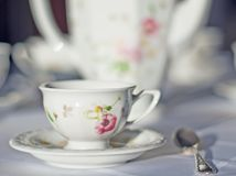 Fine porcelaine cup and silver spoon on table. Table set with white tablecloth and china. Fine porcelaine coffee cup and silver spoon in  short focus Stock Images
