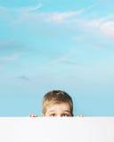 Fine portrait of a small boy hiding behind a board. Fine portrait of a small boy hiding behind an empty board Stock Photo