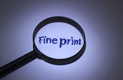 Fine print. Inscription word magnified under a magnifying glass Royalty Free Stock Image
