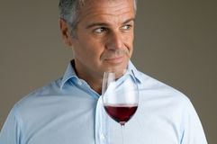 Fine red wine glass. Satisfied mature sommelier smell at a glass of a red wine Stock Photo