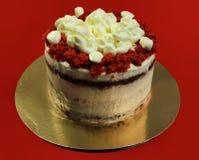 Fine rossa del dolce del velluto su su un piedistallo dorato e su un fondo rosso Fotografie Stock