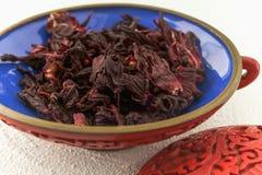 Fine rossa del tè dell'ibisco su in una ciotola su un tavolo da cucina immagini stock libere da diritti