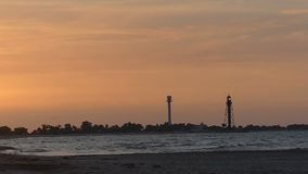 Fine seascape with a tower and a lighthouse in the background