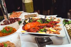 Fine selection of crustacean for dinner. Lobster, crab and jumbo shrimp on a white plate.  Stock Image