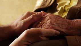 Fine senior della pelle della grinza della mano della tenuta del giovane della donna anziana su 2 archivi video