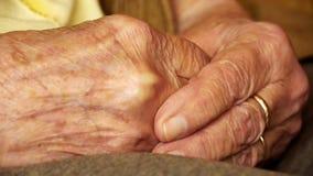 Fine senior della pelle della grinza della mano della tenuta del giovane della donna anziana su stock footage
