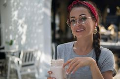 Fine smiling young woman poses outdoors with pink cocktail in hands, royalty free stock photography