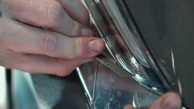 Fine in su Applicazione del film protettivo sui fari dell'automobile La mano ha tagliato con un coltello PPF stock footage
