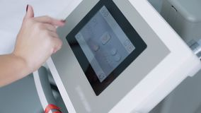 Fine su attrezzatura medica La mano femminile accende l'apparecchio elettronico per la procedura cosmetica, movimento lento stock footage