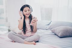 Fine su bello sveglio della foto lei i suoi earflaps delle mani dello Smart Phone della bambina imparare usura ondulata riccia di fotografia stock