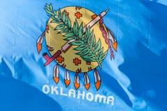 Fine su con la bandiera dello stato di Oklahoma che ondeggia nel vento fotografia stock libera da diritti