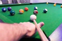 Fine su del braccio dell'uomo che gioca la tavola verde dello stagno dello snooker in una stanza moderna dei giochi fotografia stock