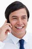 Fine in su del commerciante sorridente sul suo cellulare Fotografie Stock Libere da Diritti