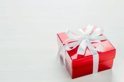 Fine su del contenitore di regalo rosso con l'arco bianco del nastro sul backgrou bianco Fotografia Stock
