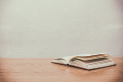 Fine su del libro aperto sullo scrittorio con il fondo d'annata della sfuocatura del filtro Immagini Stock Libere da Diritti