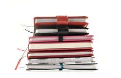 Fine in su dell'impilato di sui libri su una priorità bassa bianca Immagine Stock
