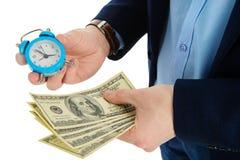 Fine su dell'uomo d'affari che giudica un orologio ed una pila di contanti disponibili, di tempo e di concetto dei soldi Prendere Fotografia Stock Libera da Diritti