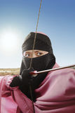 Fine su della donna musulmana asiatica pronta a sparare una freccia Immagine Stock