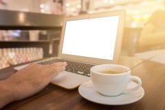 Fine su della mano dell'uomo di affari che lavora al computer portatile dello schermo in bianco nella sfuocatura del caffè o nel  Fotografia Stock