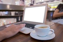 Fine su della mano dell'uomo di affari che lavora al computer portatile dello schermo in bianco nella sfuocatura del caffè o nel  Immagine Stock